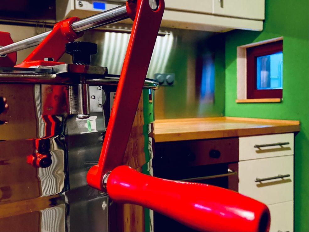 Griff einer Honigschleuder und im Hintergrund eine saubere, frisch geputzte Küchenzeile.